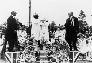The crowning of May Queen Elsie Hogg in 1925 by the 1924 May Queen Ester Elofson. Mr. May Day J.J. Johnston is the man standing to the left of her and the Master of Ceremonies that year, J.J. Cambridge is to her right