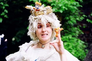 this is a picture of a woman dressed in a costume that is somewhat fairy and somewhat Mother Nature. She is gesturing with er hand and making a funny face. She is outdoors in a park.