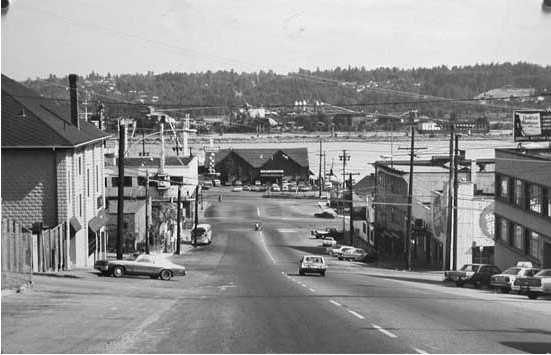 Photograph shows a street view of Eighth Street, looking toward the river, showing the intersections of 8th and Victoria, Carnarvon, Columbia, and Front streets. Shows edge of CPR station, The Old Spaghetti Factory on the right, and a full view of The King Neptune restaurant at the foot of the street.