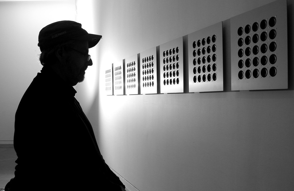 Photo by Mario Bartel Jim Johnston, a regular visitor to the New Media Gallery at the Anvil Centre, pauses to listen to the sounds emitting from tiny speakers in Tristan Perich's installation, Octave.