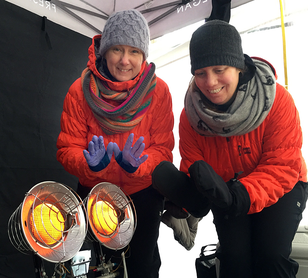 Matching puffy orange jackets and a propane space heater keep Michelle and Kathryn toasty in the Kiki Kitchen kiosk.