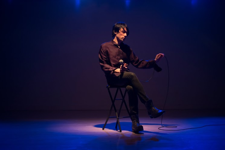 A photo of performing artist Joseph Keckler seated alone on stage with a microphone.