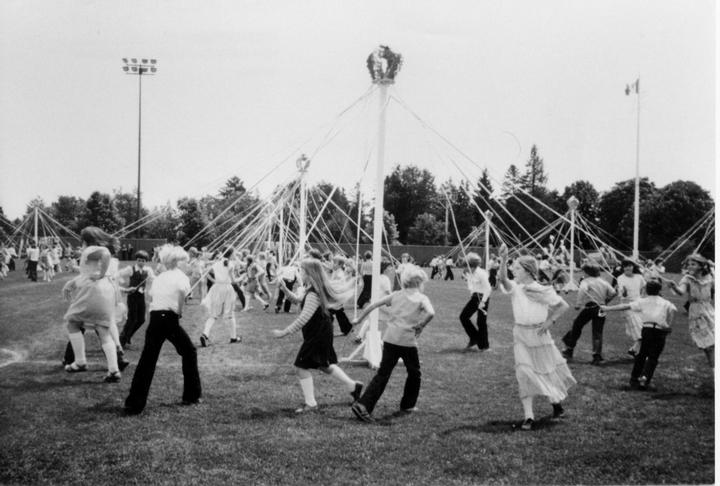 A black and white photo depicting children dancing the maypole dance in New Westminster in 1978